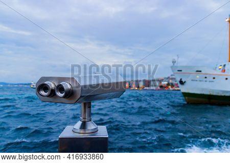 Tourist Metallic Telescope Against Blurred Sea Background. Binoculars For Sightseeing On The Embankm