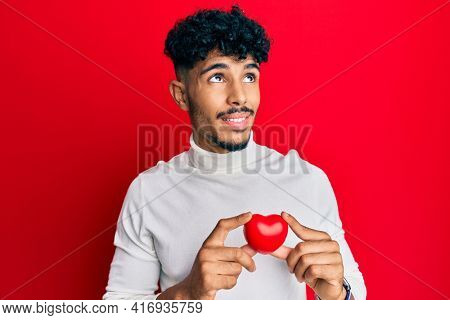 Young arab handsome man holding heart smiling looking to the side and staring away thinking.
