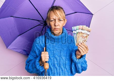 Middle age blonde woman holding umbrella and canadian dollars banknotes skeptic and nervous, frowning upset because of problem. negative person.
