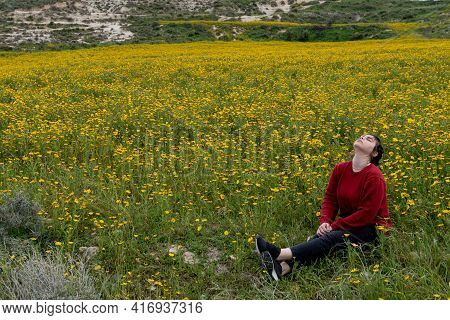 Young Woman Sitting In The Field With Yellow Marguerite Flowers Enjoying Nature In Spring.