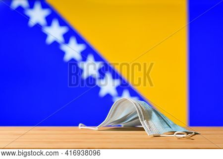 A Medical Mask Lies On The Table Against The Background Of The Flag Of Bosnia And Herzegovina. The C