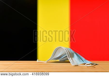 A Medical Mask Lies On The Table Against The Background Of The Flag Of Belgium. The Concept Of A Man