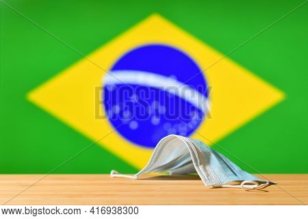 The Medical Mask Lies On The Table Against The Background Of The Brazilian Flag. The Concept Of A Ma
