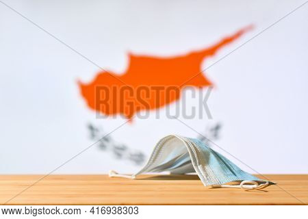 A Medical Mask Lies On The Table Against The Background Of The Flag Of Cyprus. The Concept Of A Mand