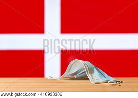 A Medical Mask Lies On The Table Against The Background Of The Flag Of Denmark. The Concept Of A Man