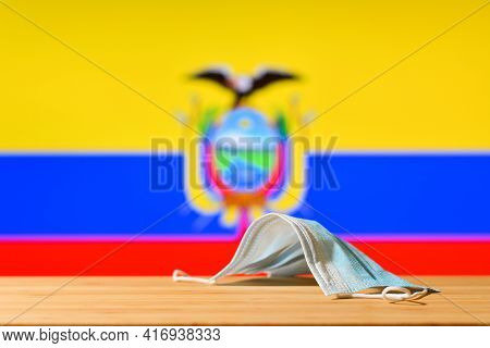 A Medical Mask Lies On The Table Against The Background Of The Flag Of Ecuador. The Concept Of A Man