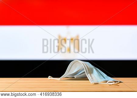 A Medical Mask Lies On The Table Against The Background Of The Flag Of Egypt. The Concept Of A Manda