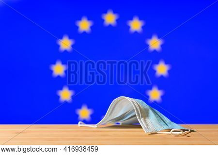 A Medical Mask Lies On The Table Against The Background Of The Eu Flag. The Concept Of A Mandatory M