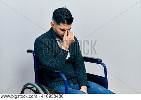 Handsome man with beard sitting on wheelchair tired rubbing nose and eyes feeling fatigue and headache. stress and frustration concept.
