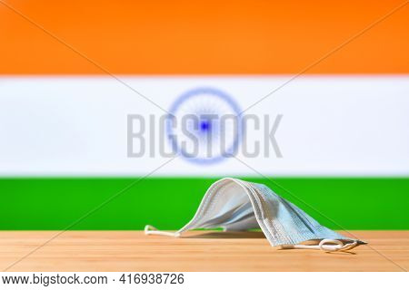 A Medical Mask Lies On The Table Against The Background Of The Flag Of India. The Concept Of A Manda
