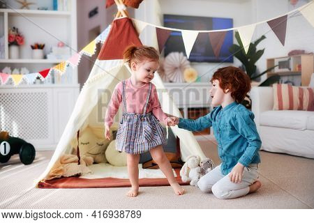 Cute Happy Siblings Playing Together In Nursery Room At Home