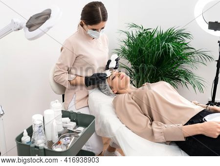 Doctor Cosmetologist Making Procedure Of Ultrasound Cleaning Of The Facial Skin In A Beauty Salon. C