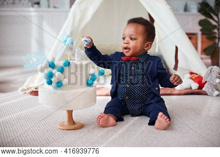 Cute One Year Old Baby Boy Having A Home Party With Birthday Cake