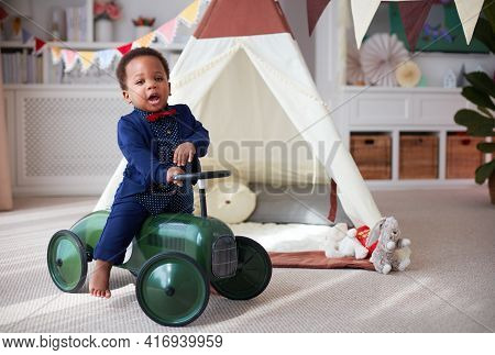 Cute One Year Old Baby Boy Having Fun On A Push Car In A Nursery Room At Home