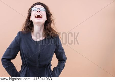 Young Beautiful Curly Hair Woman In Glasses Wearing Casual Jacket Over Beige Background Smiling And