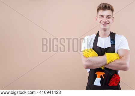 Young Smiling Man Wearing Cleaner Apron And Rubber Yellow Gloves Isolated On Beige Background. Happy
