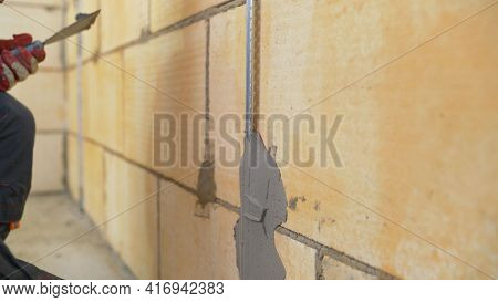 Wall Repair With Mortar. Plasterer At Work. Fastening Building Beacons To The Wall With Mortar.