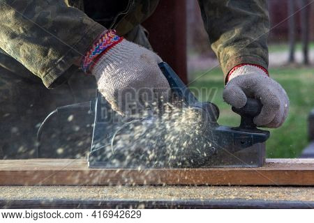 Hands Of A Joiner With An Electric Planer. Flying Shavings, Wooden Board. The Work Of A Professional