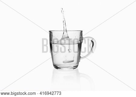 Soluble Effervescent Tablet Fallen With Splash To Transparent Glass Mug On White Background