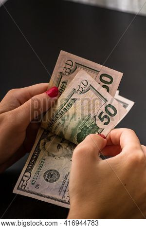 Selective Focus On Detail Of Usd Banknotes. Counting Or Giving United States Dollars Banknotes. Worl