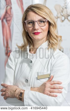 Blonde Female Physician Doctor Standing In Her Office. Portrait Of Friendly Smiling Woman-physician.
