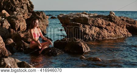 Girl Meditates On Stone. Lady In Bikini Or Alone Time. Contemplation And Relax. Leisure Outdoors. Oc
