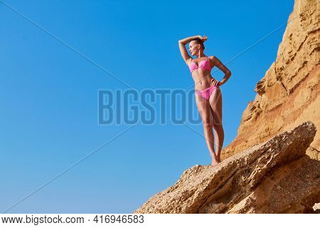 Idea Of Desire Of Adventure, Summer Time, Time To Relax And Tourism. Beautiful Woman On Top Of Cliff