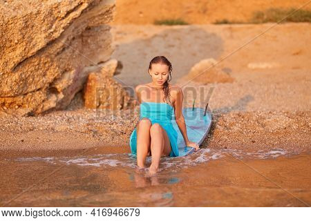 Sensual Woman In Blue Dress Sitting On Surfboard At Sea Beach. Summer Vibes, Active Lifestyle And Be