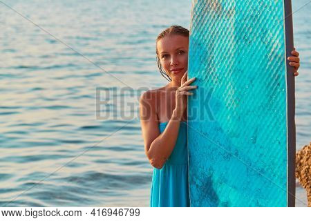 Smiling Woman Posing With Surfboard An Seashore. Happy Girl Surfer In Blue Dress. Summertime And Tim