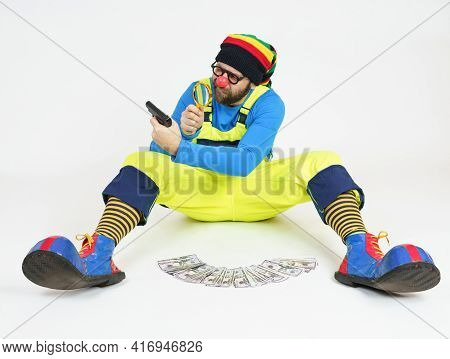 Humor And Fun Concept. A Clown In A Bright Costume Sits And Holds A Pistol In His Hands, Which He Ex