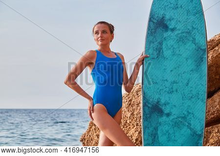 Adventure Summer Trip, Beach Relaxation And Surf Hobby Idea. Pretty Woman In Blue Swimsuit With Surf