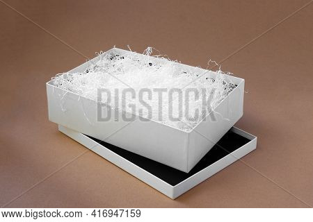 White Shredded Paper In A White Open Box On The Lid On A Paper Beige Background For Protection Durin
