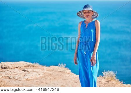 Smiling Happy Woman Posing In Blue Dress With Ocean On Background. Relax Time Vacation And Tourism C