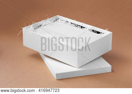 Mockup A White Open Box With Clothes In Blank White Tissue Paper And Shredded Paper For Protection O
