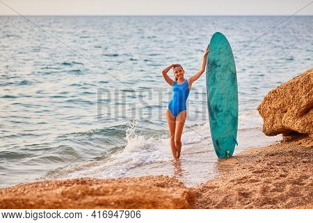 Cute Woman With Surfboard On Nature Landscape Background. Beach, Adventure Time And Summer Holiday C