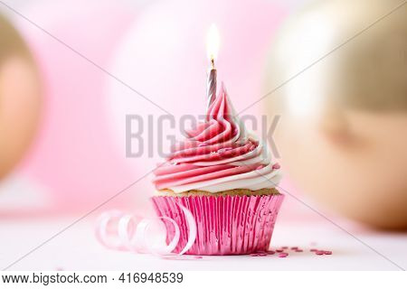 Pink birthday cupcake with one golden candle against a background of pink and gold balloons