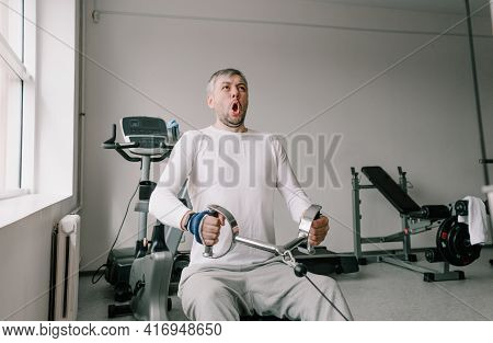 A Man With A Tense Face Performs Strength Training In The Gym. Chest Cravings. Intensive Training