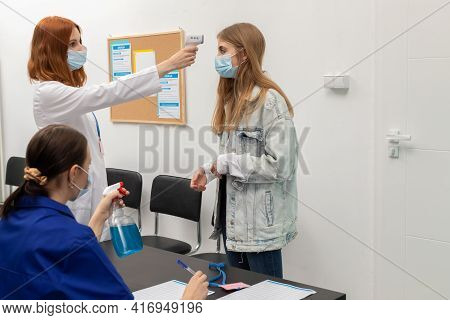 At The Entrance To The Clinic, One Person Takes The Body Temperature And Another Records Personal In