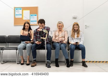 Patients Sit In A Clinic Waiting For Their Turn To Go To The Doctors Office. They Look At Their Cell
