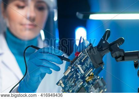 Female microelectronics engineer works in a scientific laboratory on computing systems and microprocessors. Professional electronic factory worker is testing the motherboard and coding the firmware.