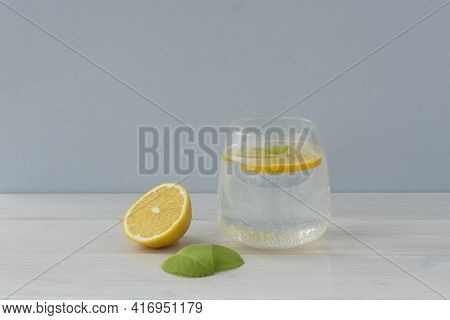 Transparent Glass Of Water With Slice Of Lemon Inside, Round Lemon Slice And Two Mint Leaves On Ligh