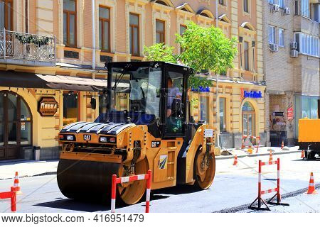 An Asphalt Roller Repairs A Road On A Historic Street. Asphalt Paver, Construction Equipment Is Repa