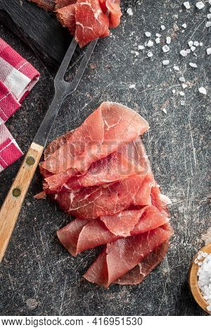 Sliced carpaccio. Raw beef meat on black table. Top view.