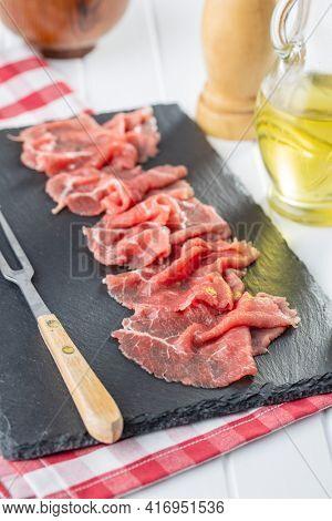 Sliced carpaccio. Raw beef meat on black cutting board.