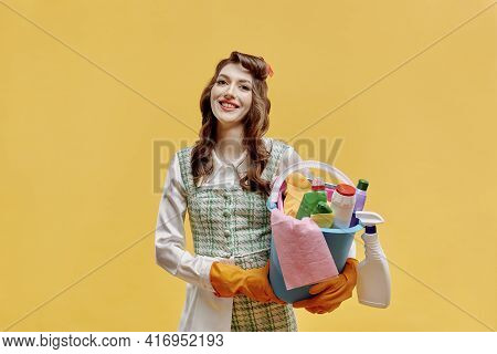 A Happy Cleaning Lady Holds A Bucket Of Cleaning Tools In Her Hands.