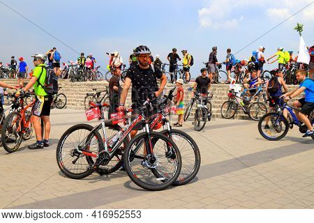 A Man In Helmet Stands Near Bicycle On The Street. People Ride Bicycles During The Cycling Festival.