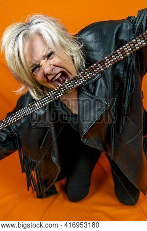 Funny Portrait Of Mature Woman. Beautiful Lady Have Fun As A Rock Star Dressed In Leather