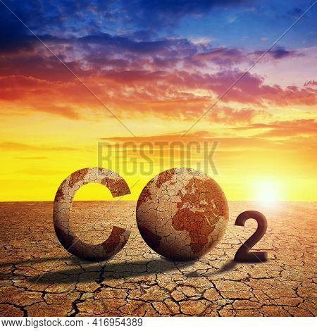 Parched planet earth in the dry landscape with cracked soil at sunset. Global warming or change climate concept. Environmental problems. Growing CO2 in the atmosphere.