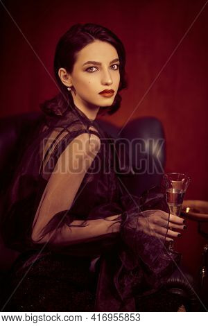 Portrait of a beautiful brunette young woman in fashionable black clothes holding glass of champagne. Beauty, fashion concept. Glamorous lifestyle.