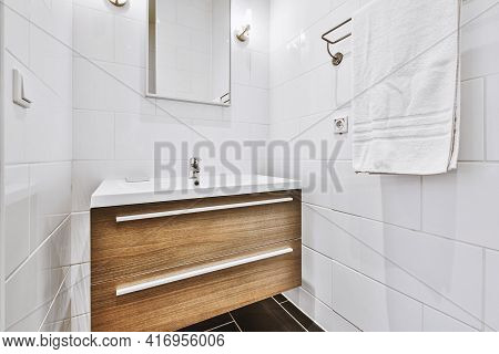Fragment Of Interior Of Modern White Bathroom With Wooden Cabinet Under Sink And With Mirror And Tow
